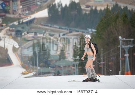 Sexy Beautiful Naked Female Skier Standing On The Snowy Slope Of The Mountain, Wearing Ski Equipment