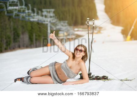 Young Sexy Naked Skier Is Lying On Snowy Slope Under Ski Lift At Ski Resort