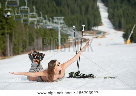 Cheerful Naked Female Skier Is Having Fun On Snowy Slope Near Ski Lift At Ski Resort