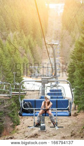 Happy Female Skier Is Sitting On Ski Lift And Riding Up To The Top Of The Mountain And Showing Thumb