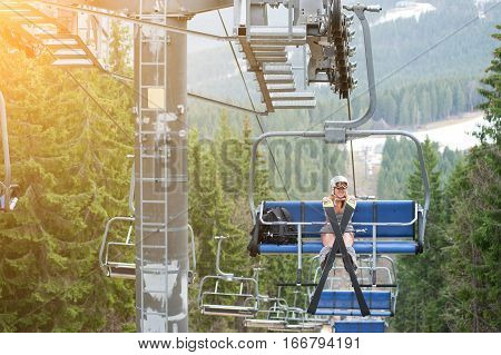 Cute Naked Female Skier Is Having Fun On Ski Lift And Riding Up To The Top Of The Mountain With   He