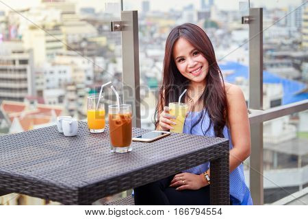 Portrait of beautiful thai asian women happy cheerful smiling sitting in a restaurant with a glass of pina colada in the hand and orange juice iced coffee on the table.