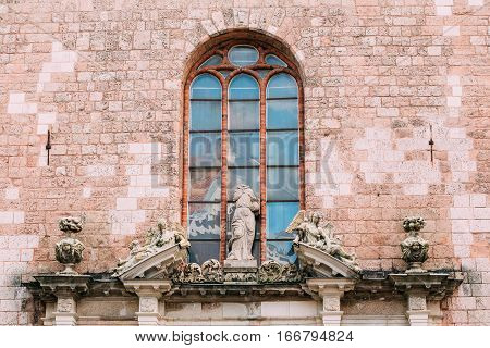 Riga, Latvia. Three Ancient Statues In Baroque Style On Top Of Portal Of Main Entrance To St. Peter Church, Famous Architectural And Historical Landmark.