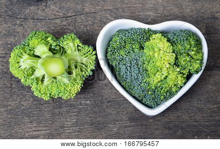 Fresh raw broccoli in a white heart shaped bowl on old wooden rustic table.Selective focus.Healthy food, raw diet or vegan food concept.
