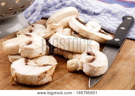 sliced mushrooms with kitchen knife and tea towel on a wooden board