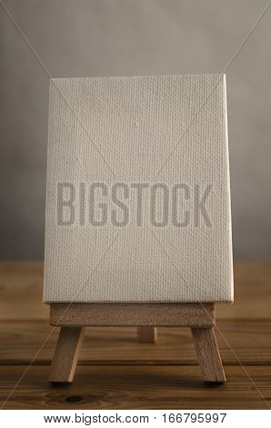 A textured white blank art canvas in portrait or vertical orientation resting on an easel on a wood planked floor. Retro hues.