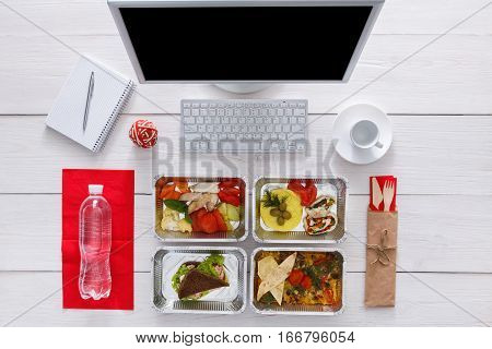 Healthy restaurant food delivery, business lunch and diet plan, fresh daily meals in office at workplace. Vegetables, meat and fruits in foil boxes. Top view, flat lay on wood