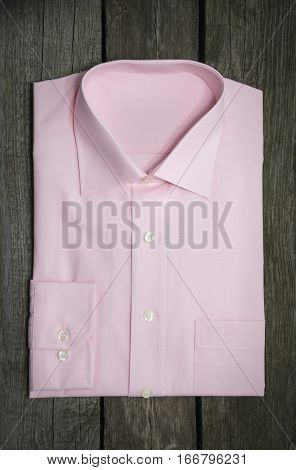 New pink shirt  on vintage wooden background.
