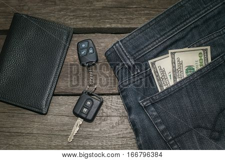 Black wallet car key and american dollar in jeans on wooden board.