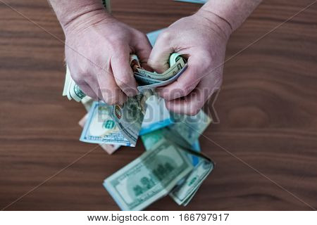 Paper money is scattered everywhere and the hand of man taking money and hold tight in your hands