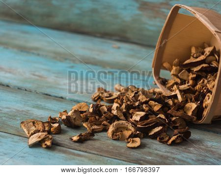 Fresh forest mushrooms in a basket on wooden table, side view.