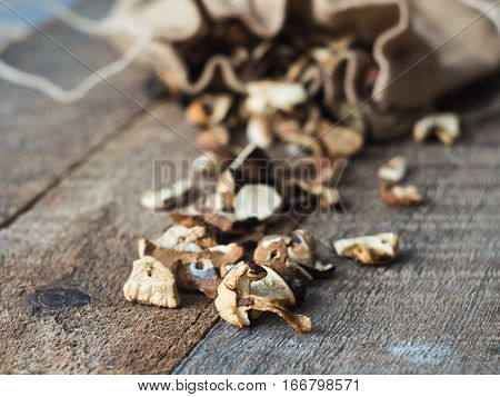 Forest Dried Mushrooms with Chanterelles, Porcini, Boletus Mushrooms and Dry Stems closeup Rustic Wooden background. Top View