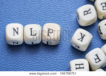 Word nlp (neiro linguistic programming) on a wooden cubes on a blue background
