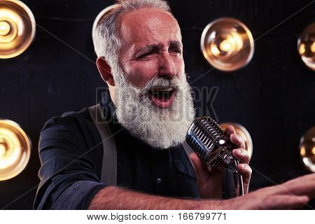 Side view of sexy singer man. Vintage style song. Live performance of exhilarated young male singer in an official wear, holding silver vintage microphone