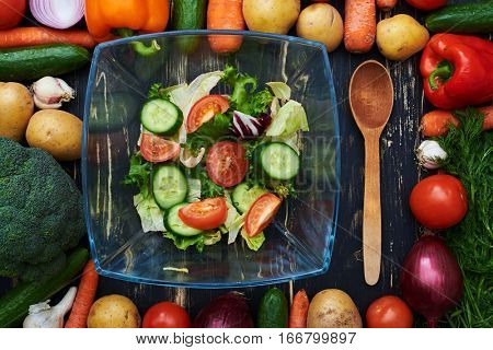Overhead view of fresh vegetable salad in a glass bow encircled in a frame made by vegetables. Wooden spoon placed near the bowl isolated on flat layout