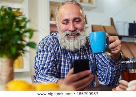 Side close-up of handsome mature man. He sits at the table. Sending message via smartphone. Enjoying morning with a cup of flavored tea. Rack focus on man. Tea, biscuits, box with lemons