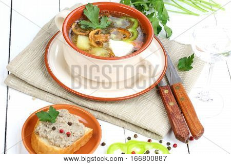 Soup from field mushrooms with a potato and greens in a ceramic cup