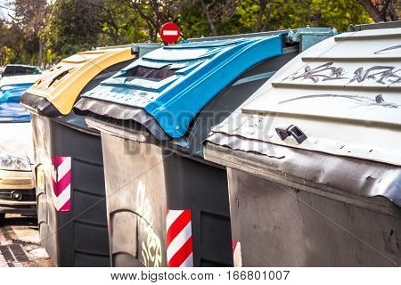 Three garbage dumpster in different colors for separate waste collection