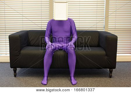 faceless   man  with blank whiteboard  -  sitting on sofa in office