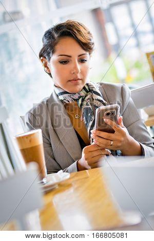 Beautiful woman using phone in cafe