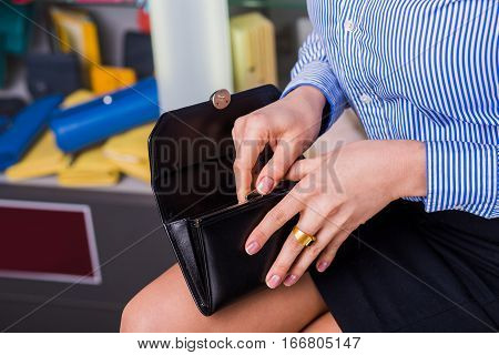 Female buyer in business clothes opens wallet, beautiful hand closeup. behind showcases with accessories. Cash payment concept.