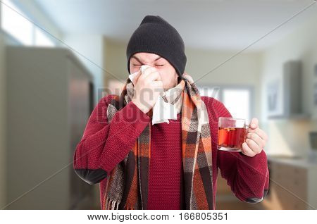 Ill Man Holding Tea Cup And Blowing Nose