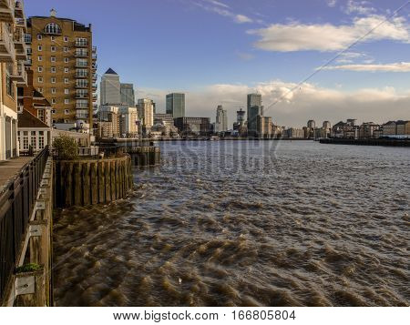 London England - December 08 2015: View to the Canary Wharf from the sandy beach of Thames River