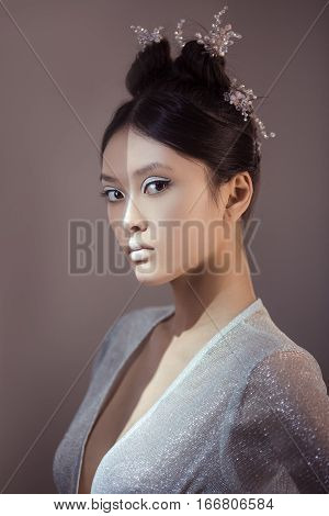 Portrait of futuristic young woman. Beautiful young multi-racial asian caucasian model cyber girl in silver urban clothes with conceptual hairstyle and make-up against blue copy-space background looking at camera. Sci-fi poster style. Half face in the sha