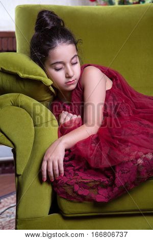 Cute lovlely tired middle eastern girl with dark red dress and collected hair sleeping on green uncomfortable sofa at home interior. studio shot.