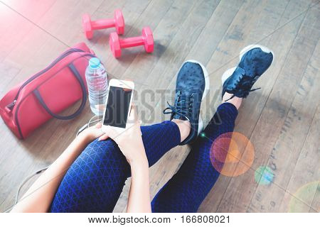 Female fitness using mobile phone after workout