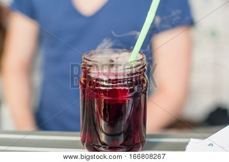 Close Up Refreshing Berry Lemonade With Dry Ice In A Glass Jar With A Straw On Display At A Street M