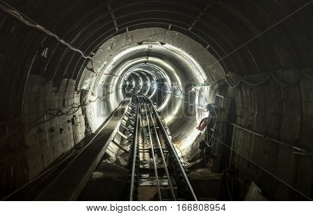 Underground mine pit tunnel gallery with working rail tracks - Industrial concept with transport and connection under earth