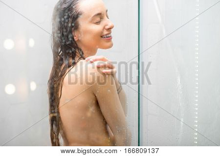 Sensual portrait of young woman taking a shower. Body and skin hygiene