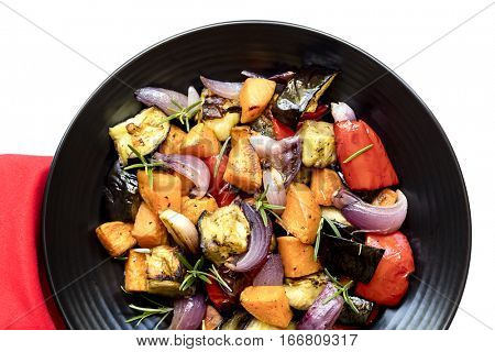Roasted vegetables on black platter.  Top view over white with red cloth.