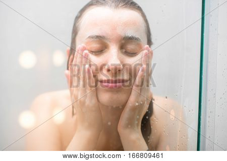 Close-up portrait of a woman with soap on her wet face standing behind the glass in the shower. Image with soft focus