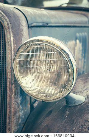 Color Toned Close Up Picture Of An Old Rusty Car Headlamp.