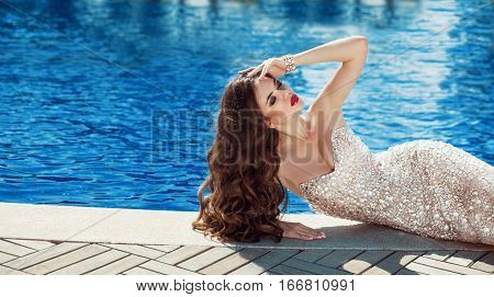 Beautiful Woman In Elegant Dress. Sexy Brunette Lying By Blue Swimming Pool. Fashion Outdoor Portrai