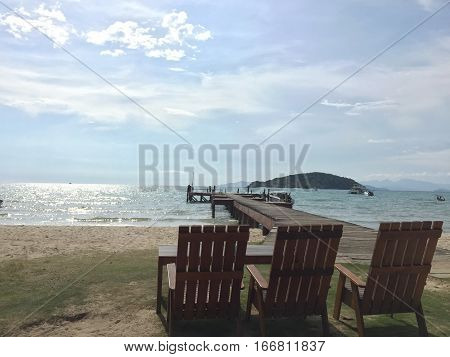 Three wooden chairs on the sea beach.