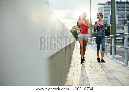 Women Jogging In City In Dusk