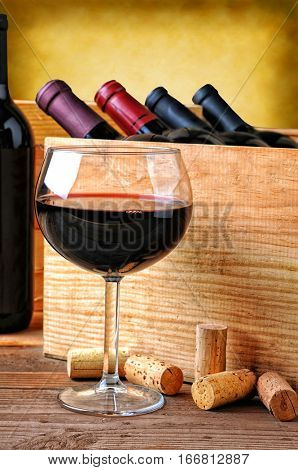 Closeup of a wine glass full of red wine. A wood crate of wine bottles in the background with warm tones and copy space.