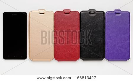 Set of color leather cases for smartphone on a white background