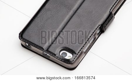 Smartphone in black leather cover, back view isolated on white background