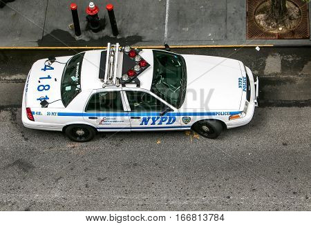 New York, September 18, 2016: An NYPD cruiser is parked by the curb, aerial view.
