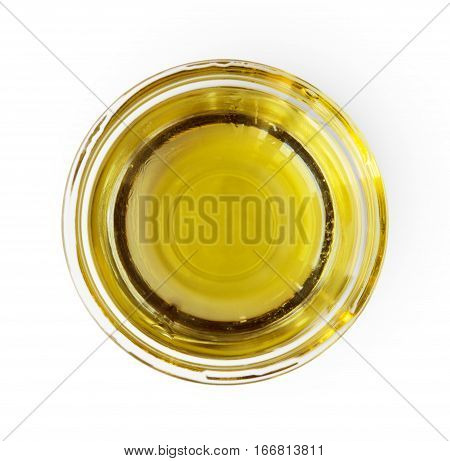 Closeup of olive oil in gravy boat or glass sauce server, top view isolated on white