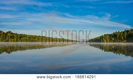 Bright mid-summer blue sky, misty morning in the middle of Corry lake.   Warm water and cooler air at daybreak creates misty patches along shoreline.  Still water along a calm, quiet lakeside.