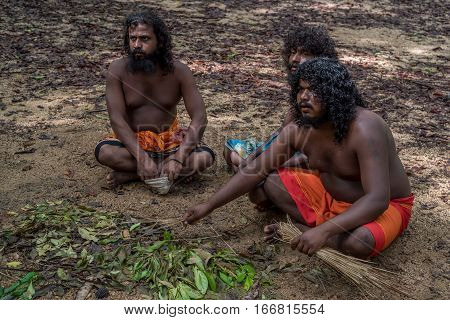 DABANA, SRI LANKA - CIRCA DECEMBER 2016: Vedda men sitting on ground. Veddas are an indigenous people of Sri Lanka living in tribes in the jungle