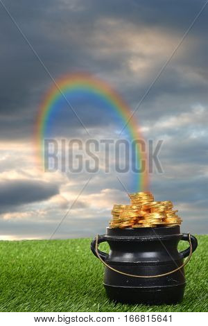rainbow leading to pot of gold on grass