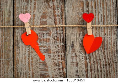 Red paper heart hanging on wood background