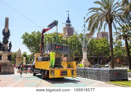 Barcelona, Spain - May 27, 2016: Worker removes portable metal fences from ground into a special cargo transport.  The alley between Triumphal arch and Parc de la Ciutadella