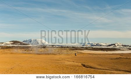 Hot springs and boiling mud pits of a geothermic area contrast with snowy mountains on the background at Hverarond in the Myvatn region of North Iceland